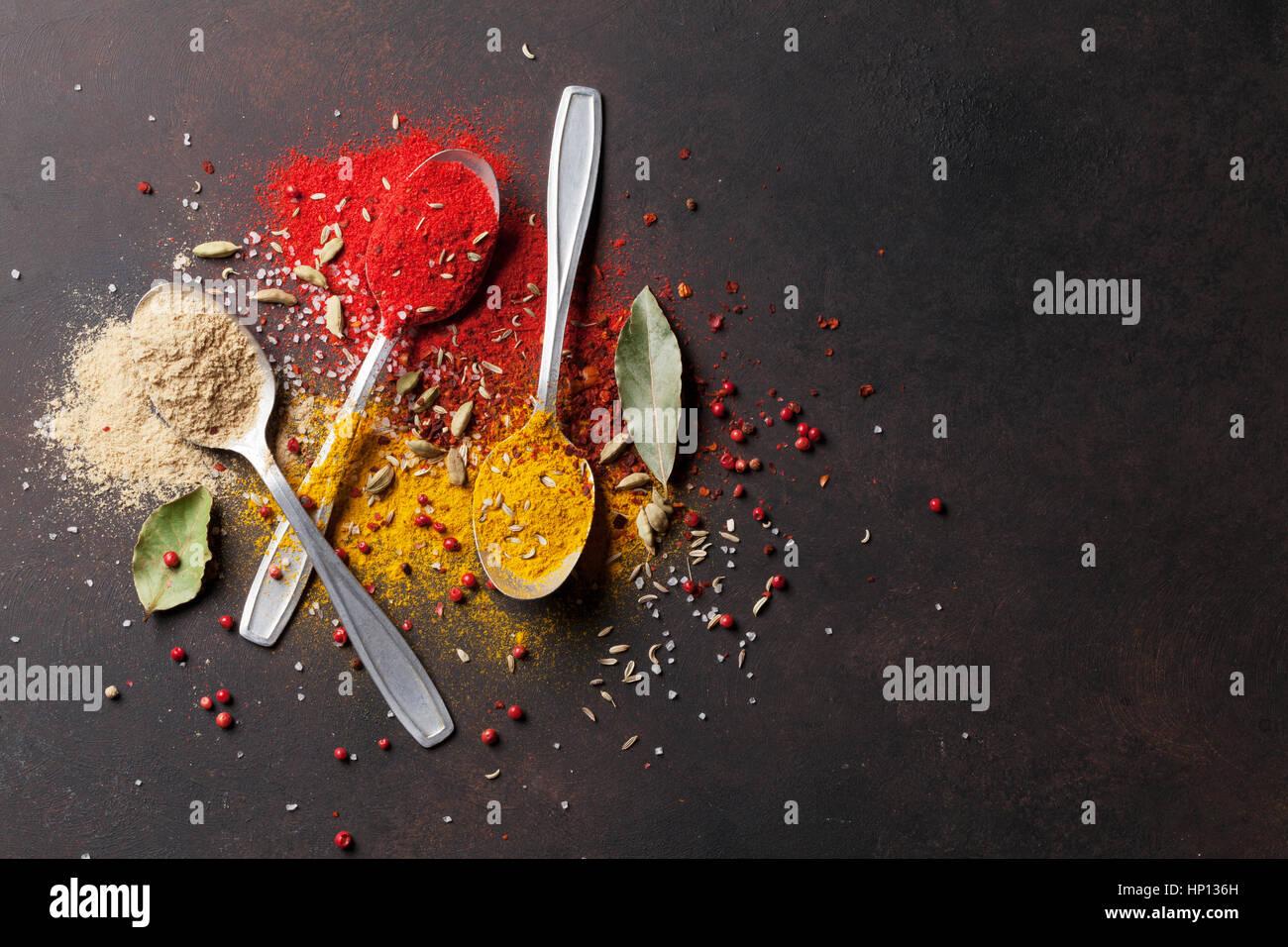 Diversas especias cucharas sobre la mesa de piedra. Vista superior con espacio de copia Imagen De Stock