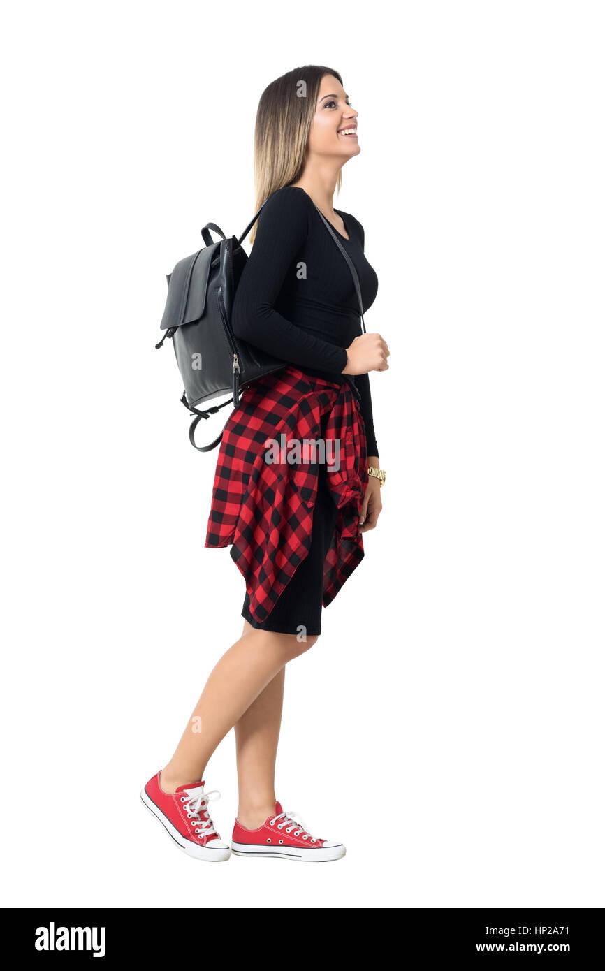 d437c9257 Feliz joven mujer street style en zapatillas y vestido rojo caminando vista  lateral. Longitud de