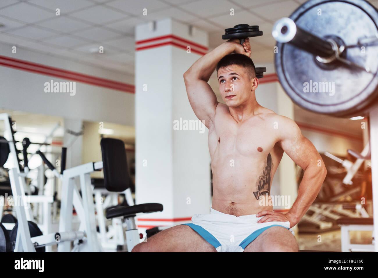 Hermosa culturista athletic guy, realiza ejercicios con d Imagen De Stock