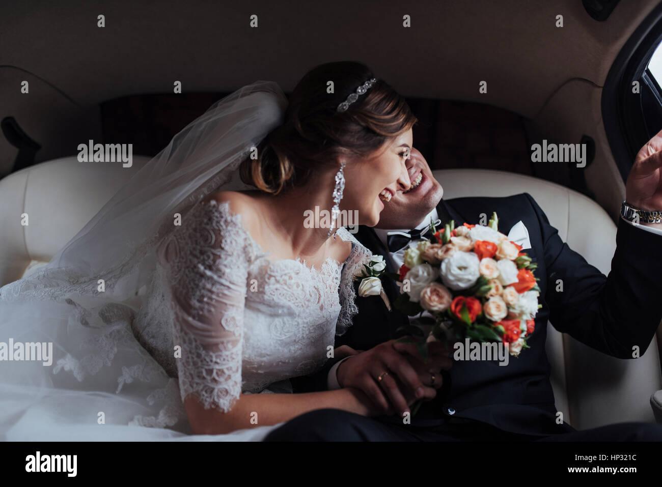 Pareja joven en un coche en el día de la boda. Imagen De Stock