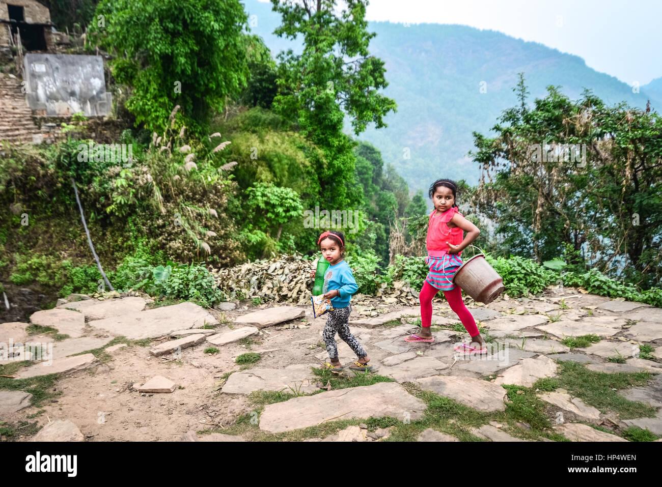 Niñas nepalesas ir a la fuente para tomar agua en Damdame Village, distrito de Kaski, Gandaki, Nepal occidental. Imagen De Stock