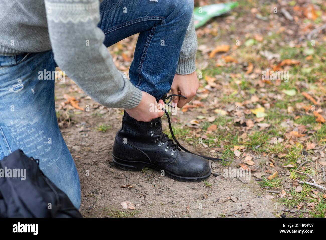 Excursionista macho en el campo shoelace atado Imagen De Stock
