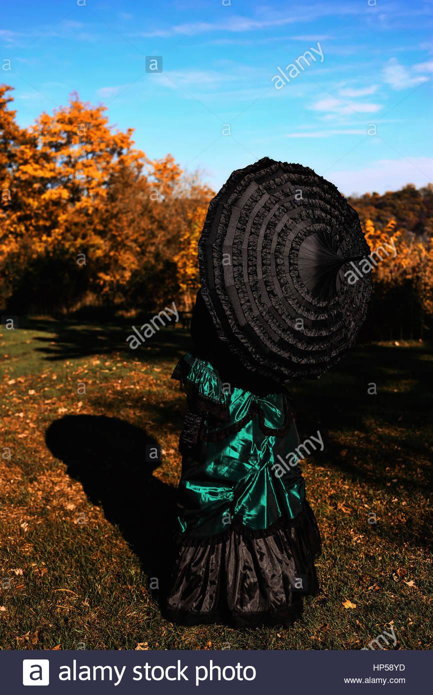 Vista trasera de la mujer Victoriana sosteniendo un paraguas Foto de stock