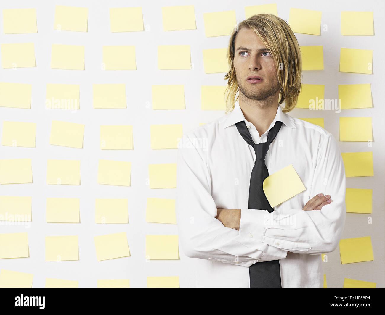 Junger Mann en Hemd und Krawatte steht vor verschraenkte Postit-Wand, Armenia (modelo-liberado) Foto de stock