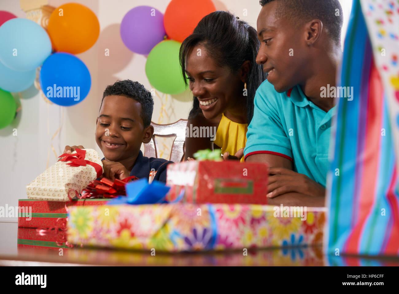 Feliz familia negra en casa. Padre afroamericano, celebrando el cumpleaños de la madre y el niño, divertirse Imagen De Stock