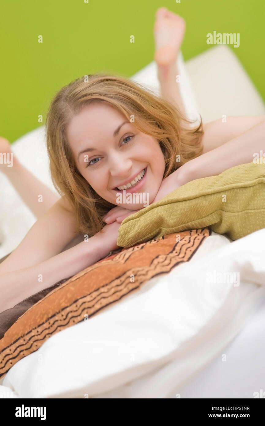 Lanzado , modelo Frau Junge, 25+, mit Kissen liegt auf dem Bett - Mujer con almohadas acostado en la cama Foto de stock