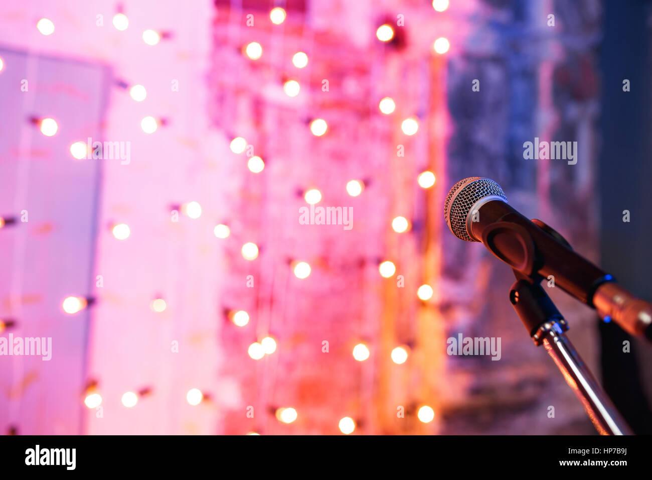 Cerca del micrófono en el Concert Hall, con luces borrosa a fondo Imagen De Stock