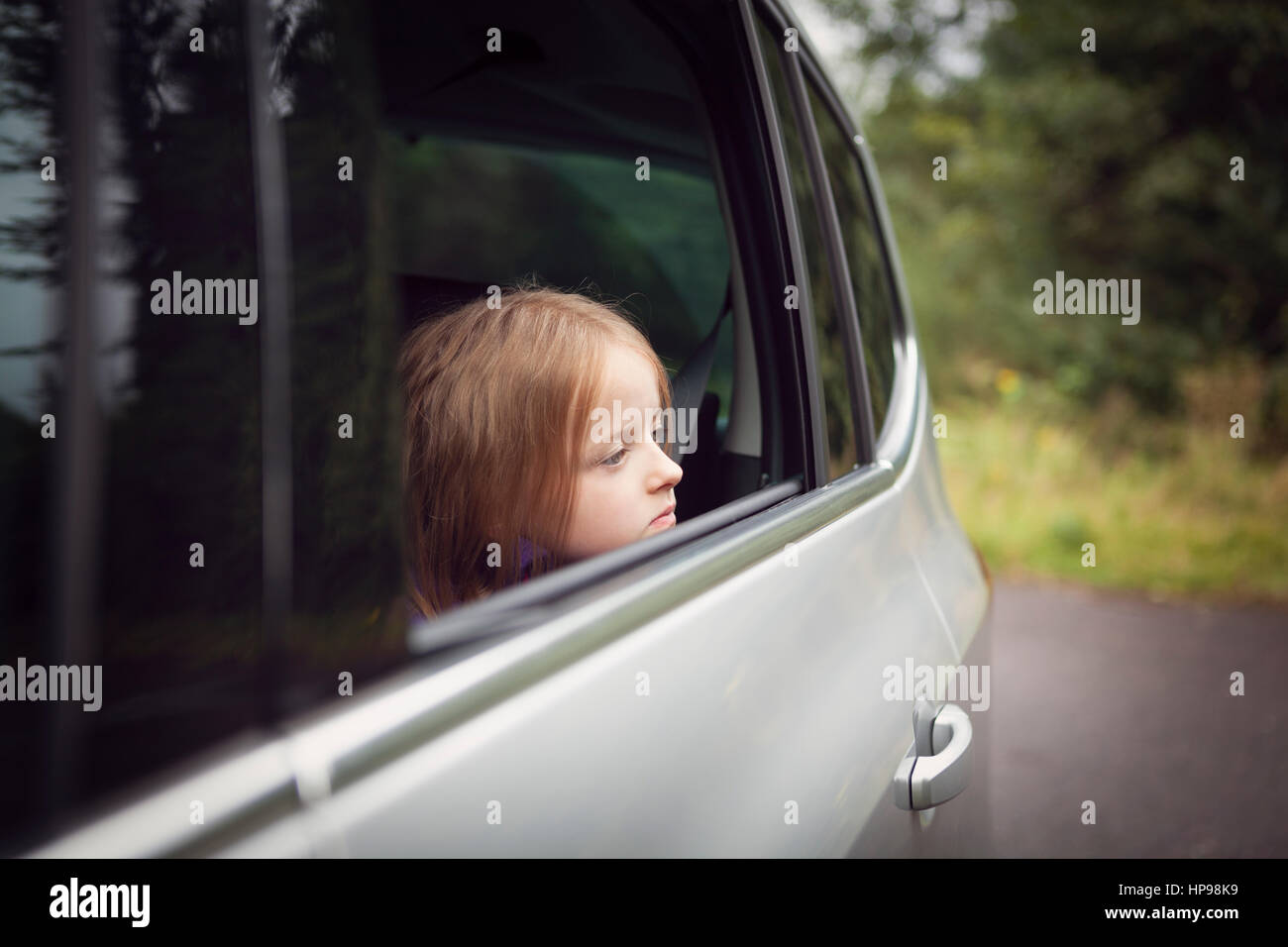 Chica busca fuera de abrir ventana de coche Imagen De Stock