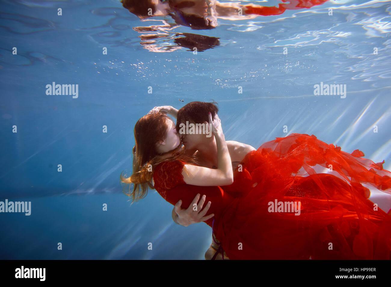 Bajo el agua en la piscina con el agua más pura. Pareja amorosa abrazarse. El sentimiento de amor y cercanía. Imagen De Stock