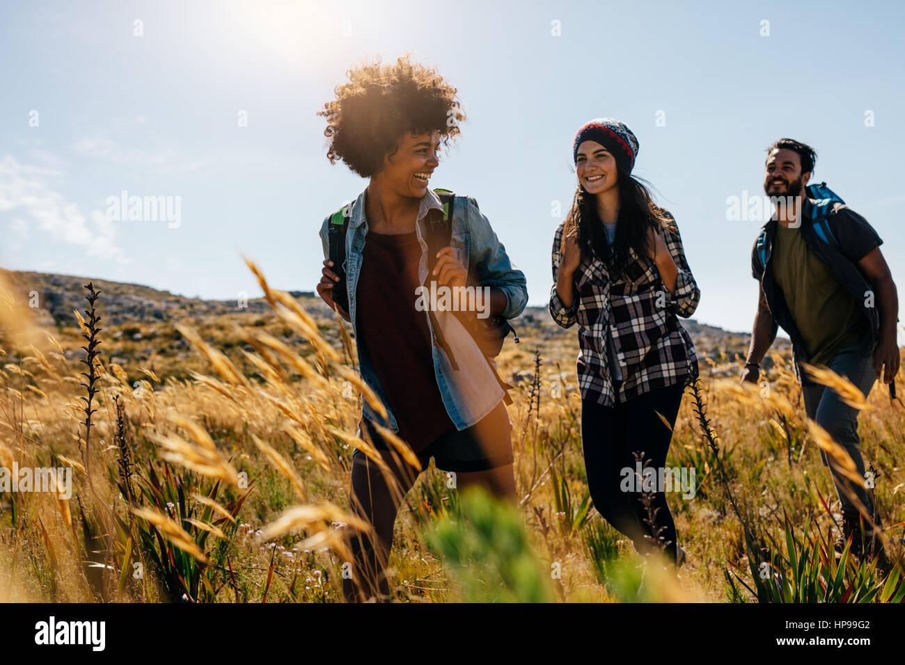 Feliz grupo de amigos senderismo juntos en un día de verano. Grupo de Amigos a pie a través de la campiña. Imagen De Stock