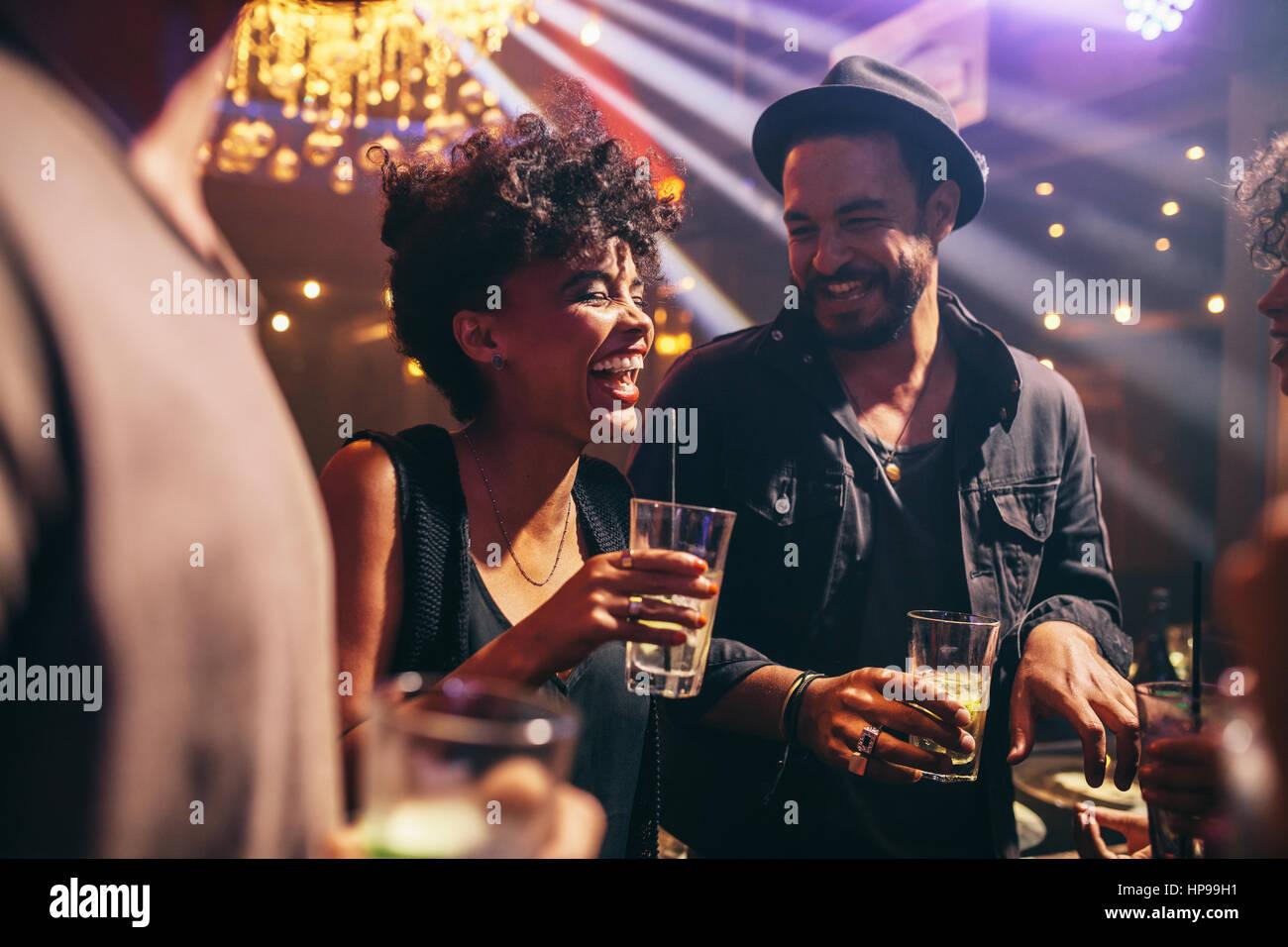 Grupo de jóvenes amigos por la noche en el pub. Feliz de hombres y mujeres jóvenes tener bebidas y sonriente Imagen De Stock