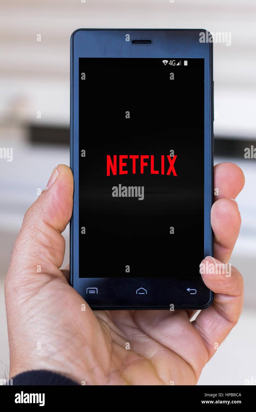 Close-up de la mano del hombre locutorio con logotipo de Netflix en la pantalla. (Editorial) Imagen De Stock