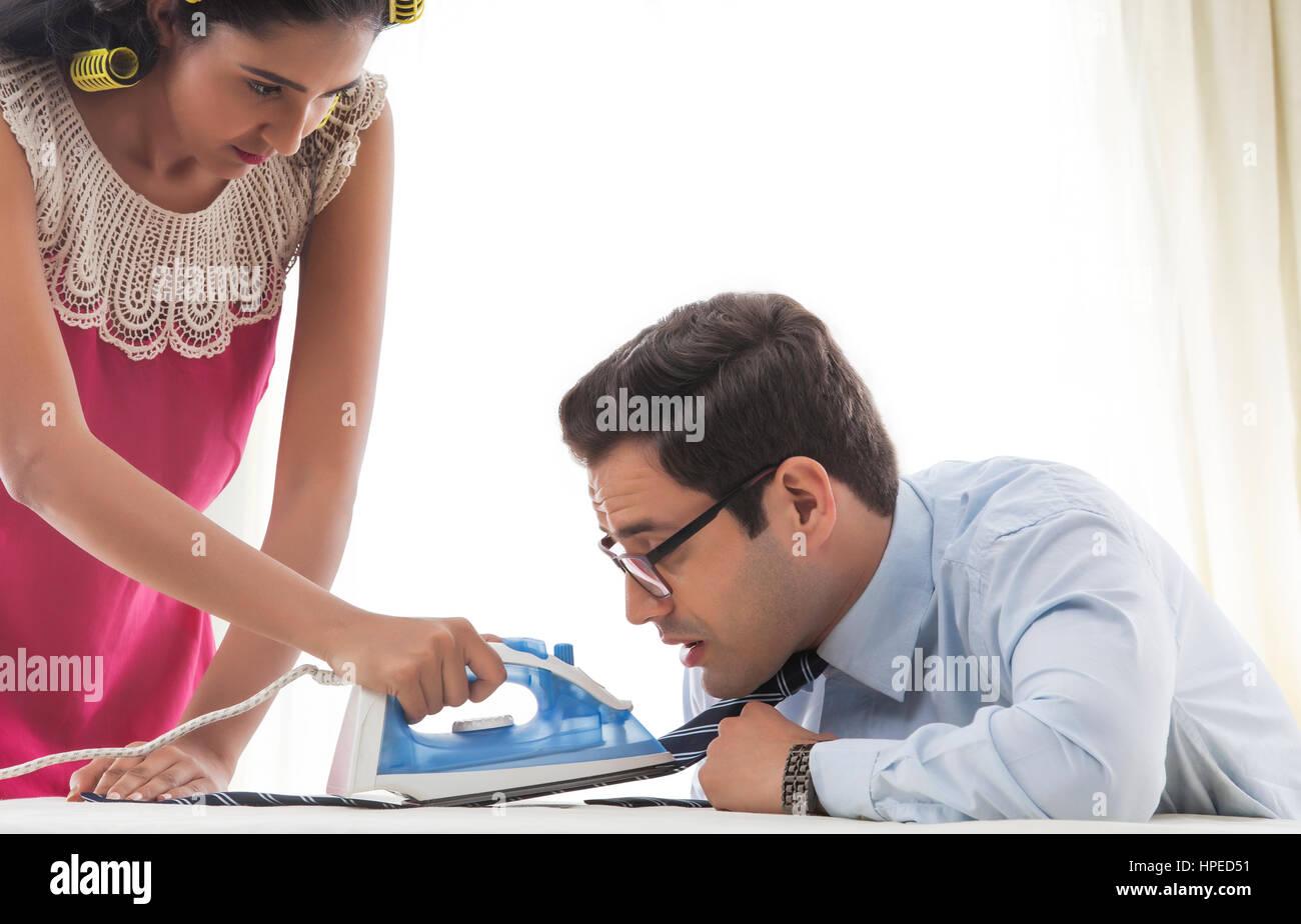 Mujer joven con rizadores de amarre del hombre de planchado Imagen De Stock