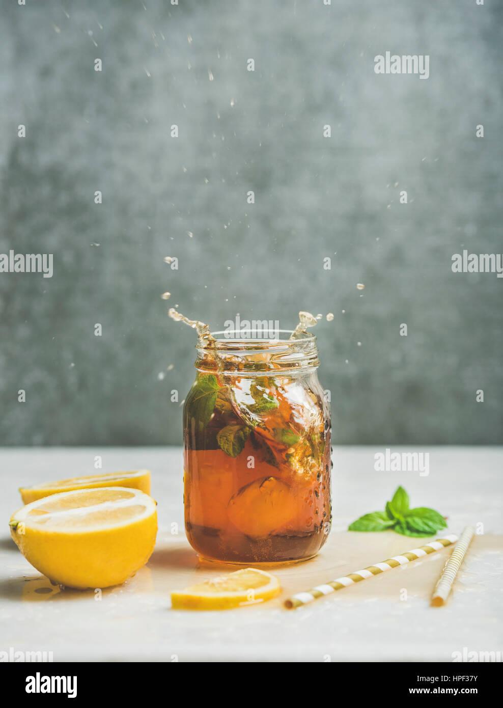 Verano frío helado de té con menta fresca, de bergamota y limón en tarro de vidrio con las salpicaduras Imagen De Stock