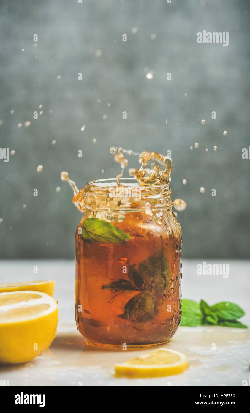 Verano frío helado de té con menta fresca, de bergamota y limón en tarro de vidrio con salpicaduras, Imagen De Stock