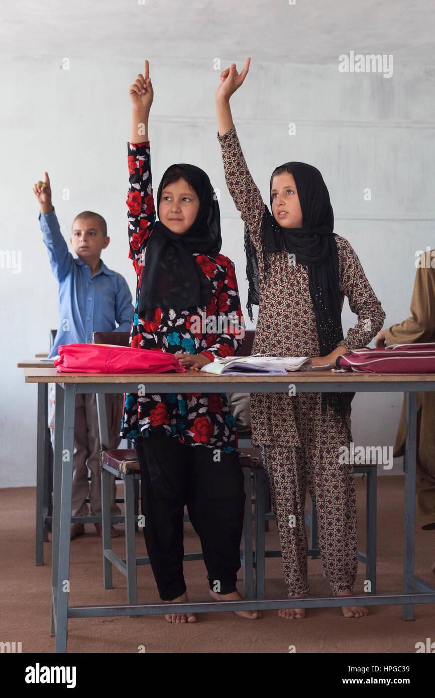 Afganistán, Kabul, en el aula de una escuela de género mixto y niños levantando sus manos Imagen De Stock