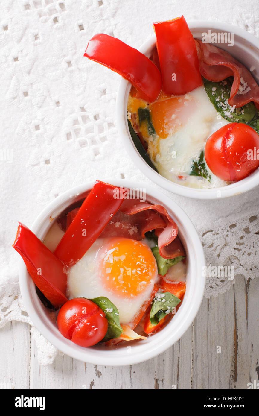 Huevo frito con espinacas, pimientos, tomates y queso en una taza de cerca en la tabla. vista vertical desde arriba Foto de stock