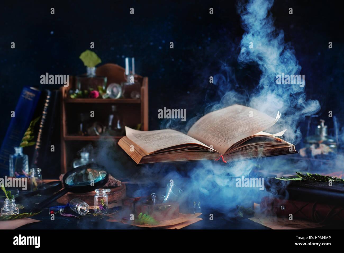 Bodegón con levitar libro de hechizos, frascos y botellas sobre un fondo oscuro con aumento de humo místico Foto de stock