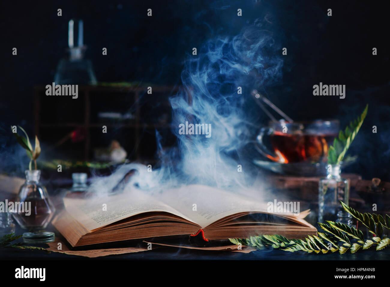 Bodegón con Abrir libro de hechizos mágicos, humo, hierbas, té y herramientas de brujería Imagen De Stock