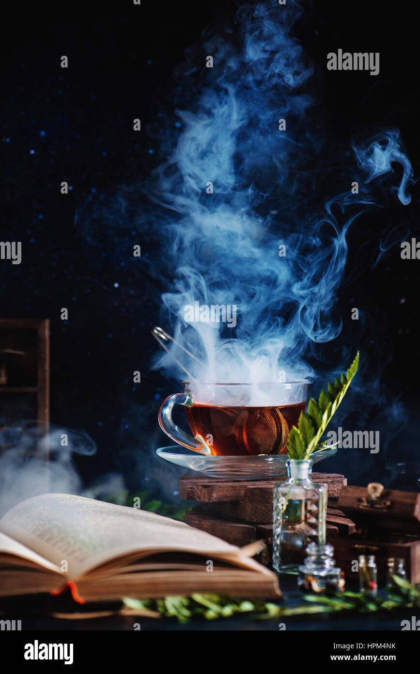 Una taza de té con un denso vapor, un libro abierto, botellas de vidrio y de hierbas en un fondo oscuro Imagen De Stock