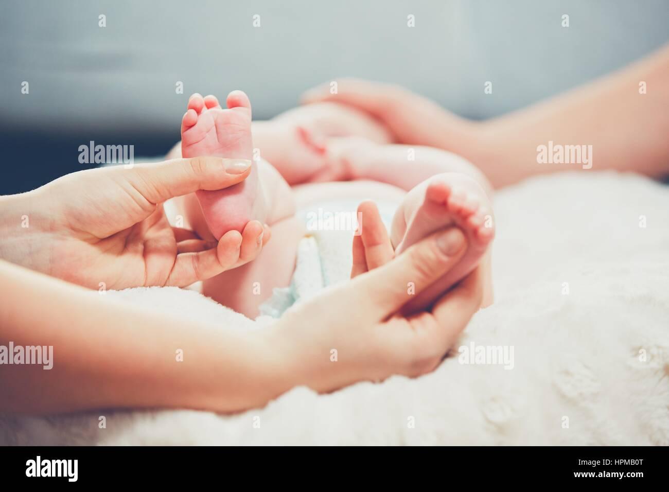 Toque de amor del Padre. Par acariciar su pequeño bebé en la cama. Imagen De Stock