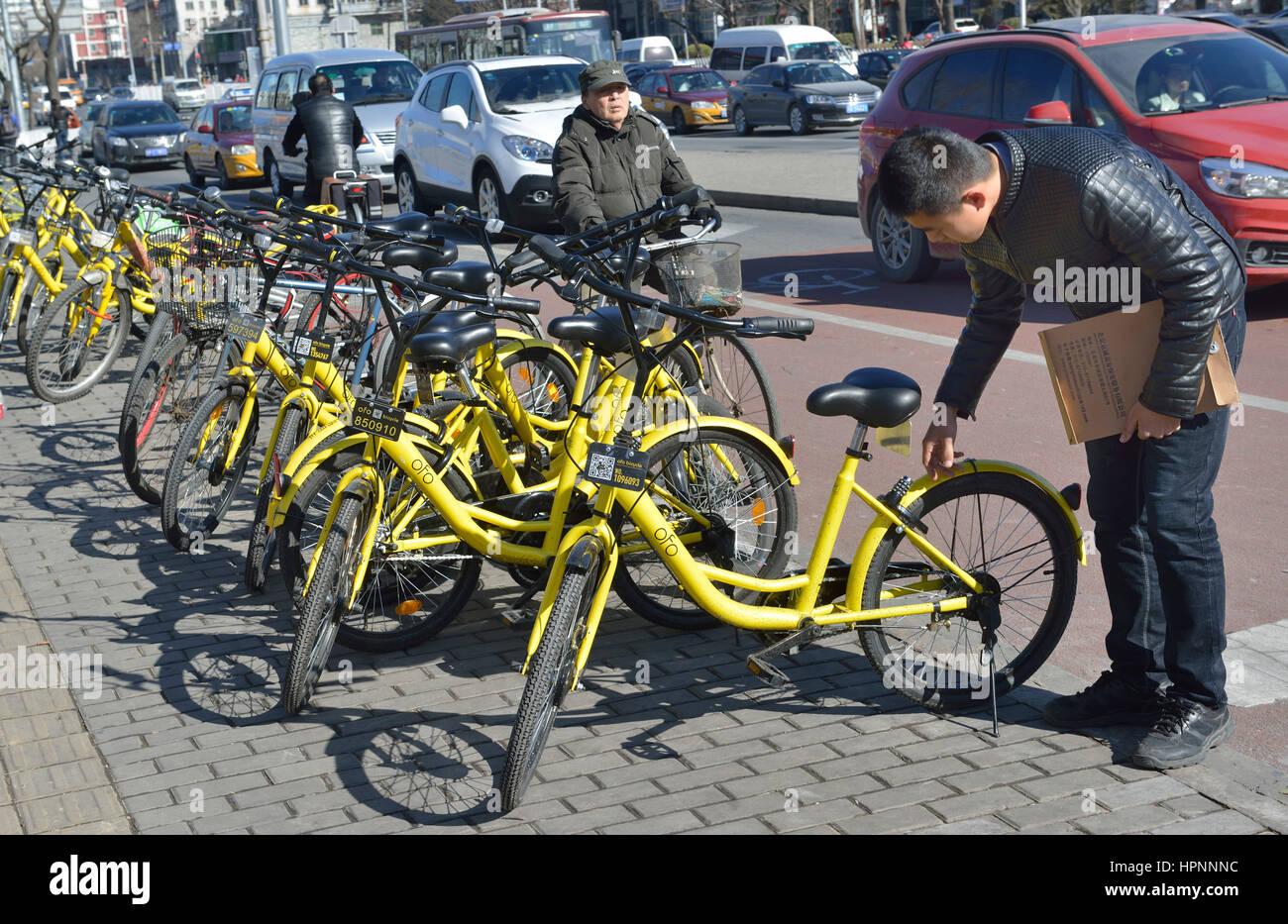 El hombre utiliza el Ofo bicicletas compartidas app para alquilar una bicicleta en Beijing, China. Imagen De Stock