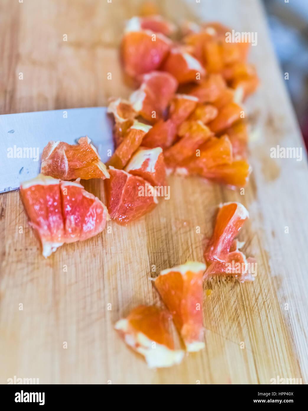 Cara Cara picada naranja en junta de bambú con un cuchillo Imagen De Stock