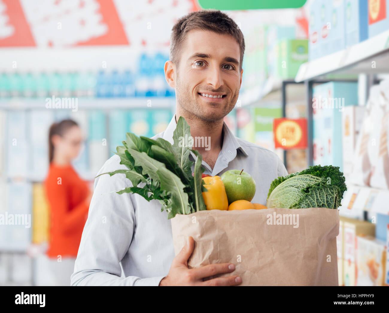 Joven comprar verduras orgánicas frescas en el supermercado