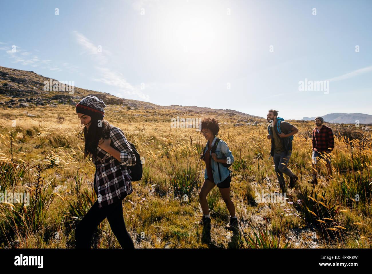 Grupo de jóvenes en el país camine. Los jóvenes, hombres y mujeres, el senderismo en un día Imagen De Stock