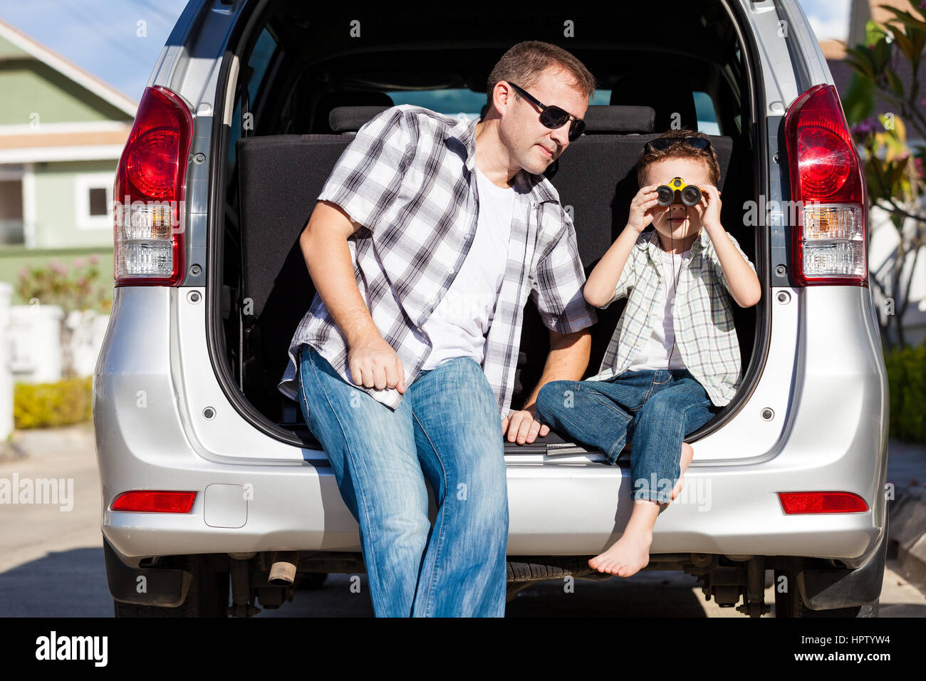 Feliz padre e hijo preparándose para el viaje por carretera en un día soleado. Concepto de ambiente familiar. Imagen De Stock