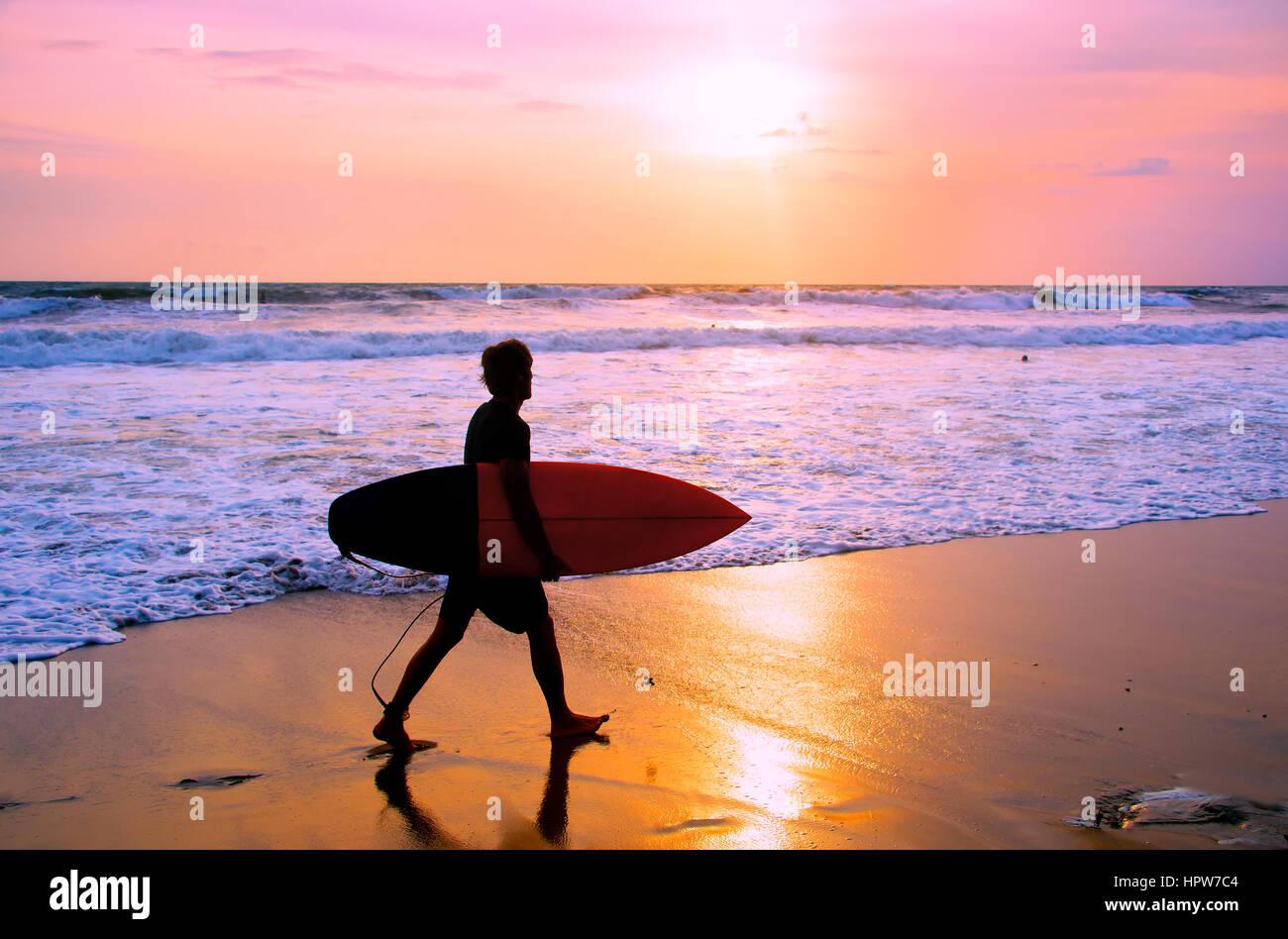 Surfer con surfboard caminando por la playa al atardecer. La isla de Bali, IndonesiaFoto de stock