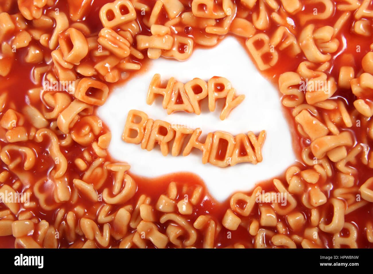 Feliz Cumpleaños escrito en letras de pasta spaghetti rodeado con letras desordenadas. Imagen De Stock