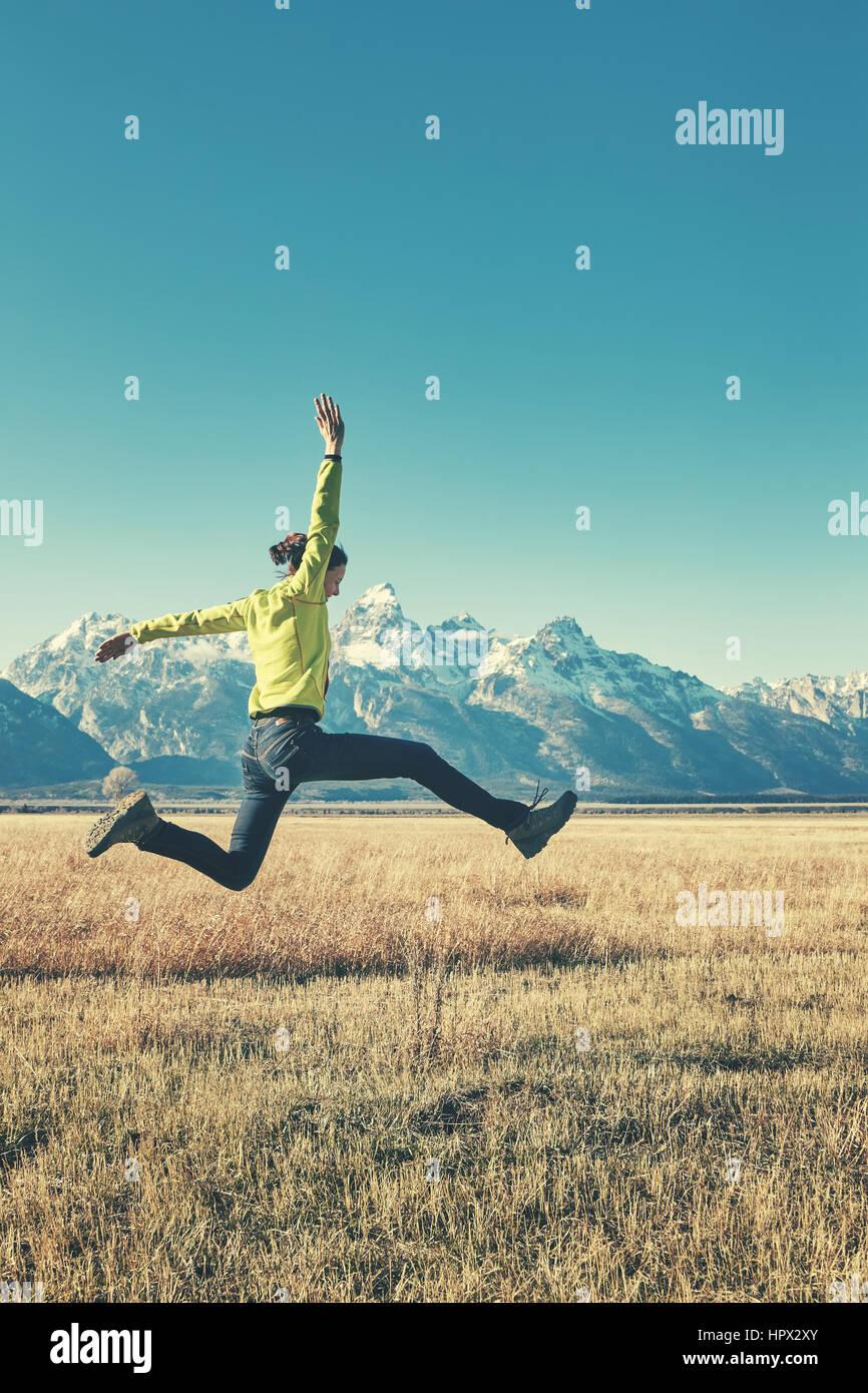 Retro estilizada imagen de una mujer joven feliz saltando en una pradera de montaña, parque nacional Grand Teton, Foto de stock