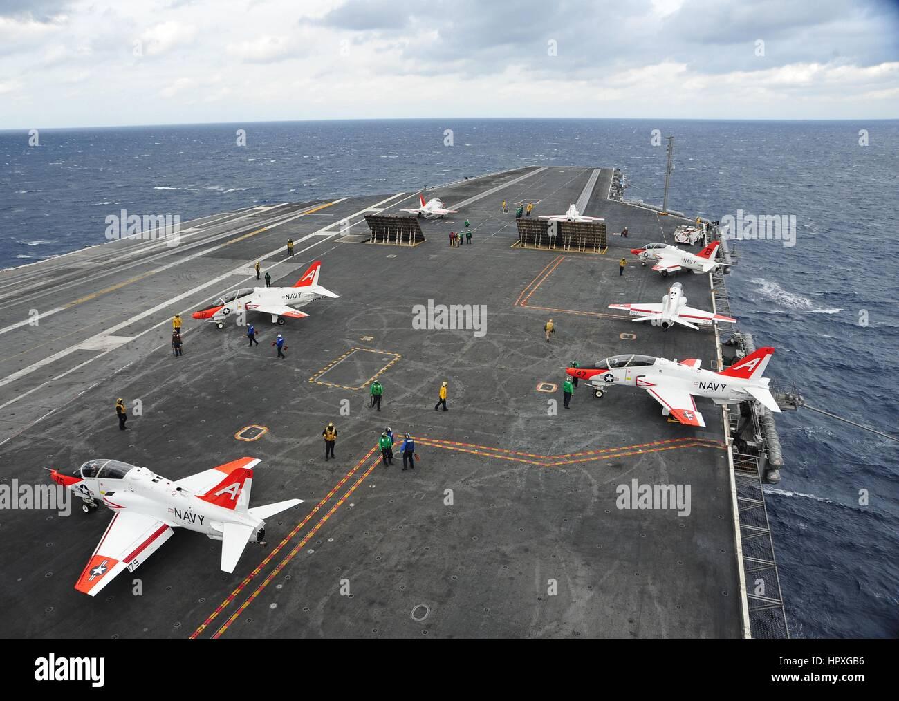 Tres aviones de prepararse para lanzar fuera de la cubierta de vuelo del portaaviones USS Harry S. Truman, en curso Imagen De Stock