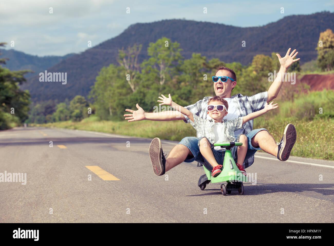 Padre e hijo jugando en la carretera en el día. Concepto de ambiente familiar. Imagen De Stock