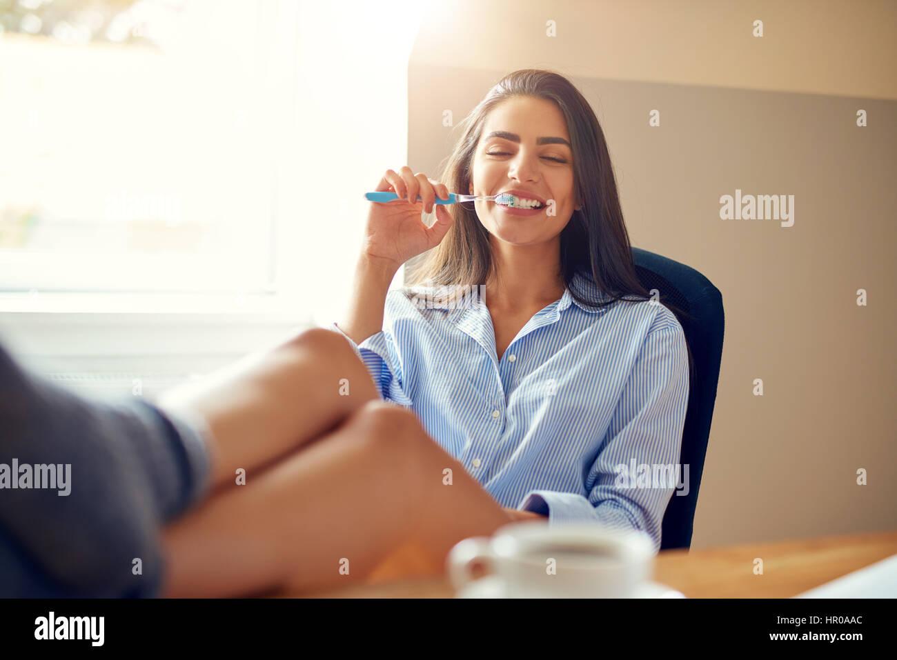 Feliz relajado joven empresaria con sus pies en el escritorio y una taza de café, trabajando en una oficina Imagen De Stock