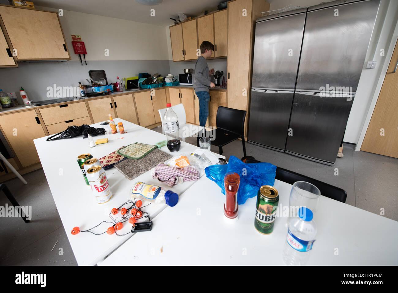 Sucio desordenado estudiante cocina compartida con pilas de lavado por el fregadero y una mesa comunal plagado de Foto de stock