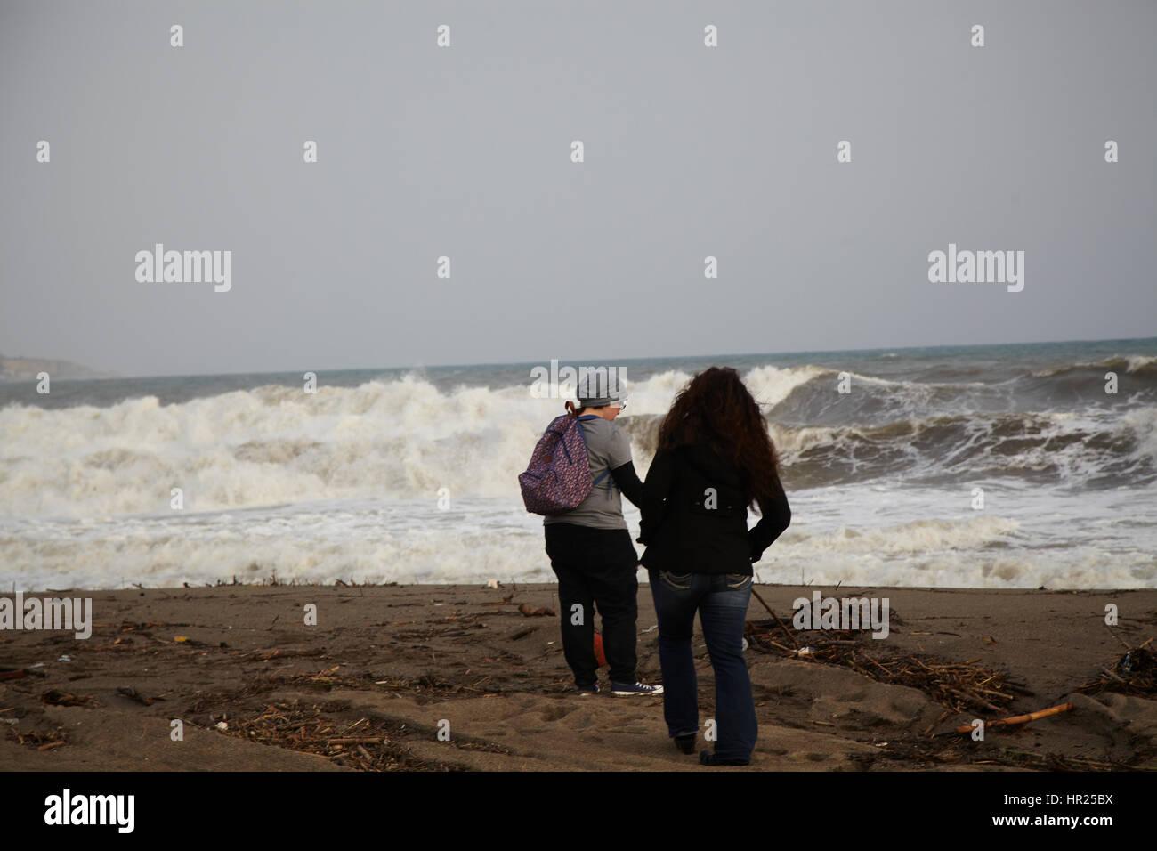 Dos chicas que buscan att grandes olas en la playa de Málaga. Foto de stock