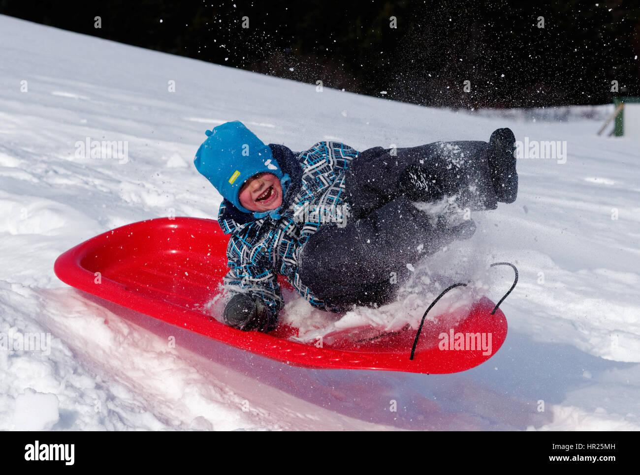 Un joven (4 años) saltar en el aire en un trineo en invierno Quebec Foto de stock