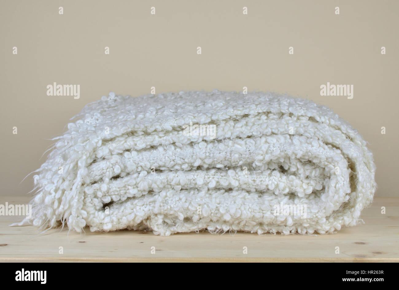 Manta de lana suave blanco con apariencia acogedora en estante de ...