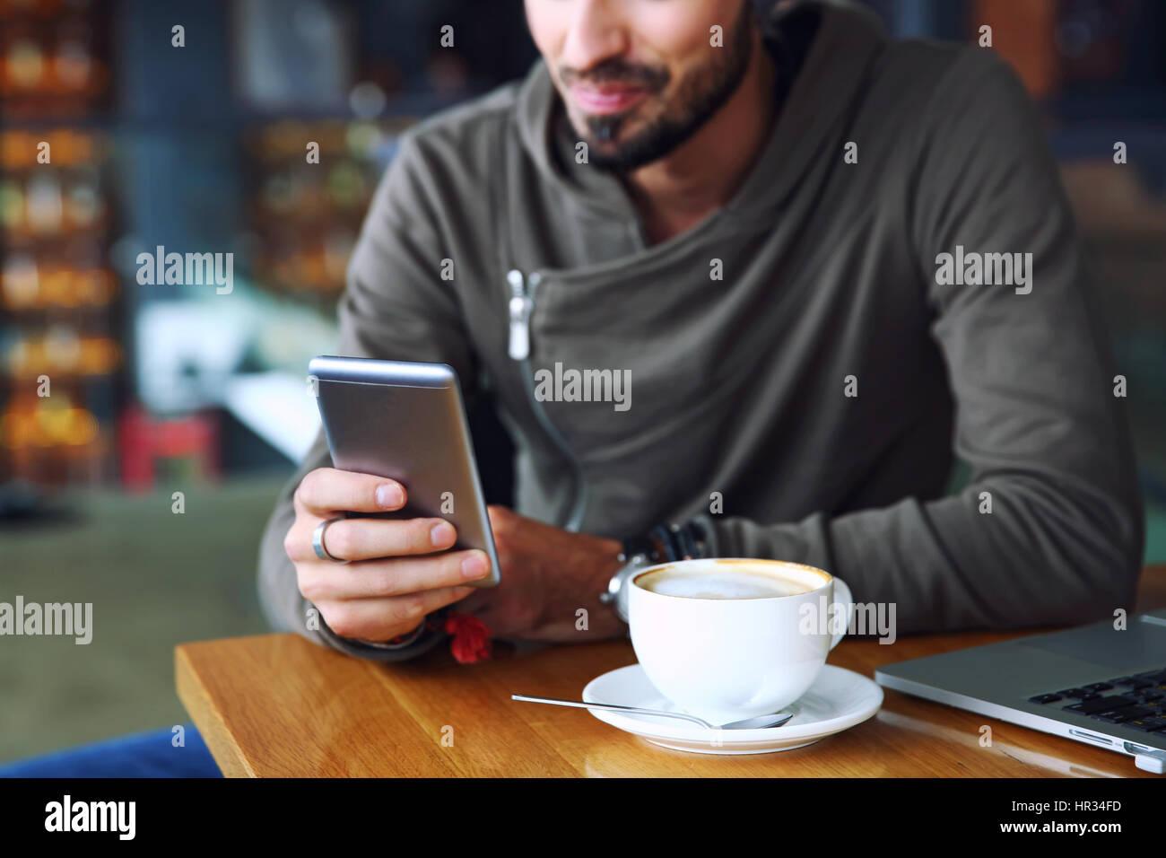 Joven apuesto alegre hipster guy en el restaurante mediante un teléfono móvil, las manos cerca. El enfoque selectivo. Foto de stock