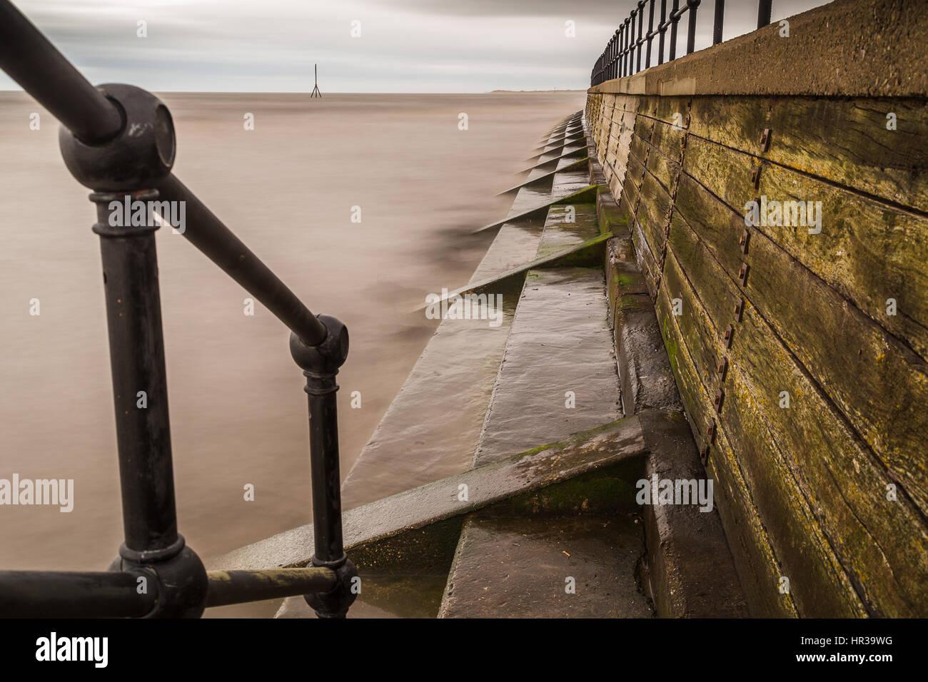 El agua golpea contra los pasos del muro de contención en la costa de Sefton en marea alta. Este fue capturado en Foto de stock