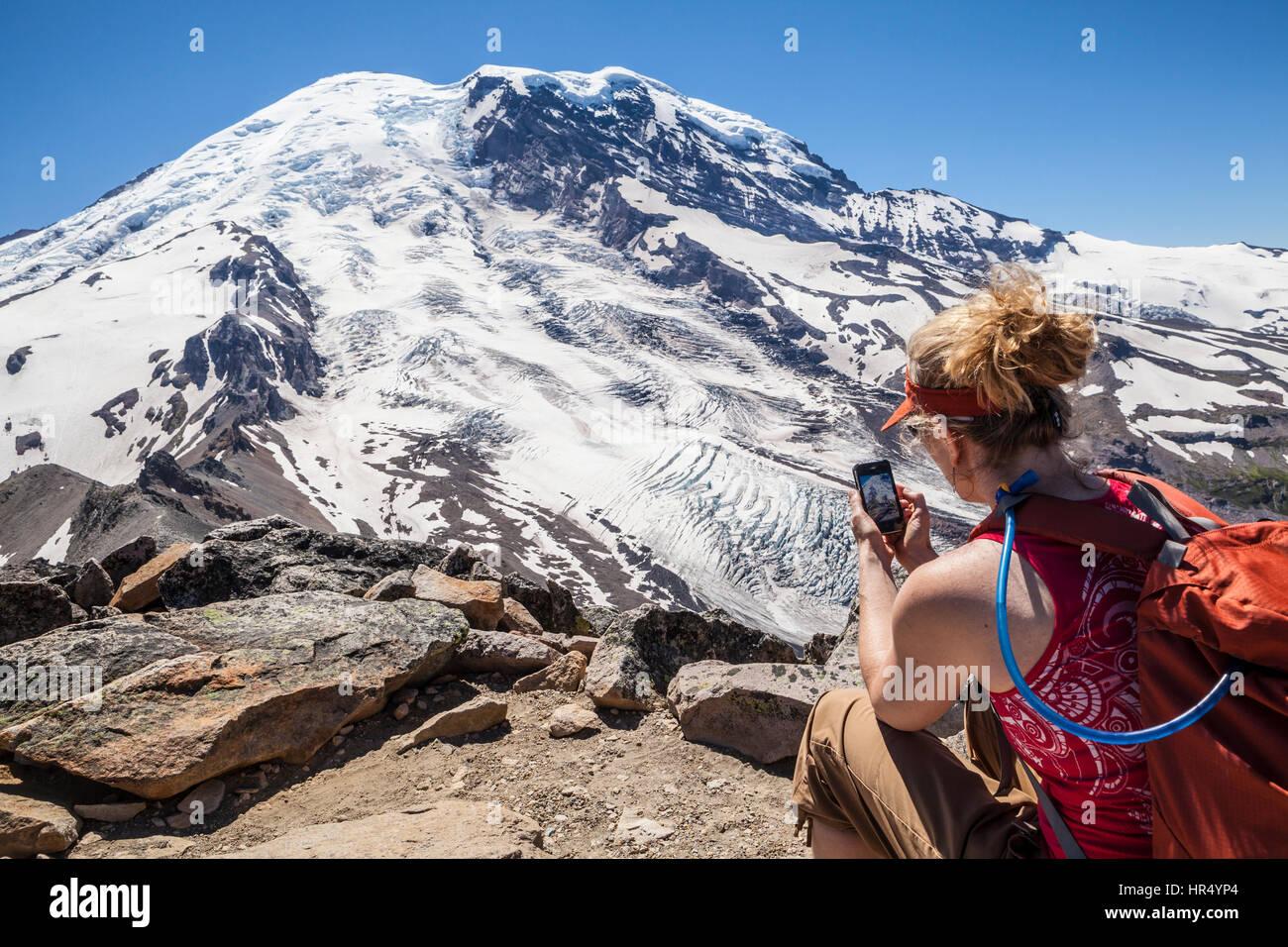 Una mujer en la cima de la montaña Burroughs tomar una fotografía con su teléfono celular, el Parque Nacional Monte Rainier, Washington, EE.UU. Foto de stock