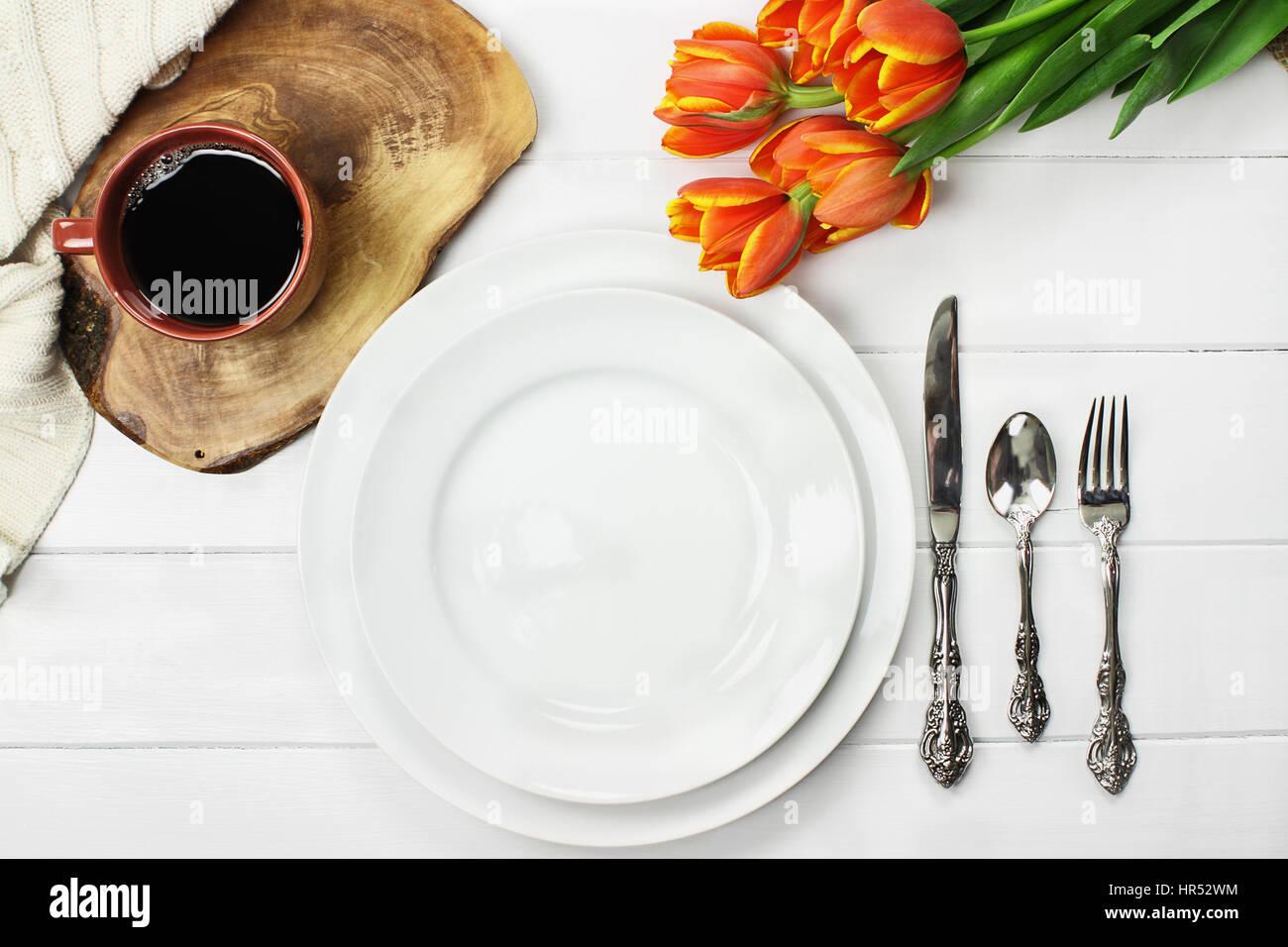 Fotografía cenital vacía por un plato de comida con un café y un Ramo de tulipanes de primavera sobre una mesa de Foto de stock