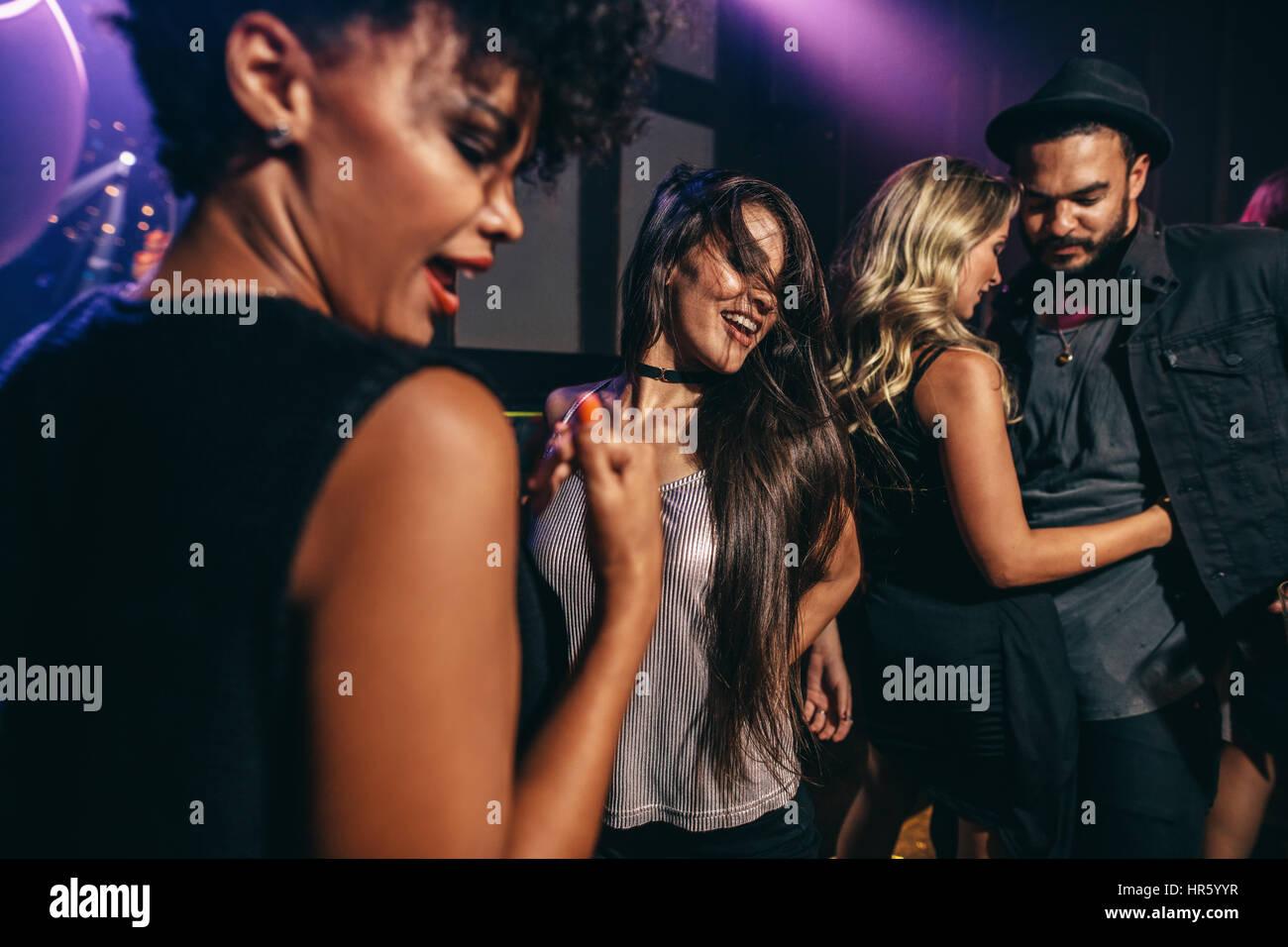 Grupo de jóvenes amigos divirtiéndonos juntos en el club nocturno. Hombres y mujeres bailando en la discoteca. Imagen De Stock
