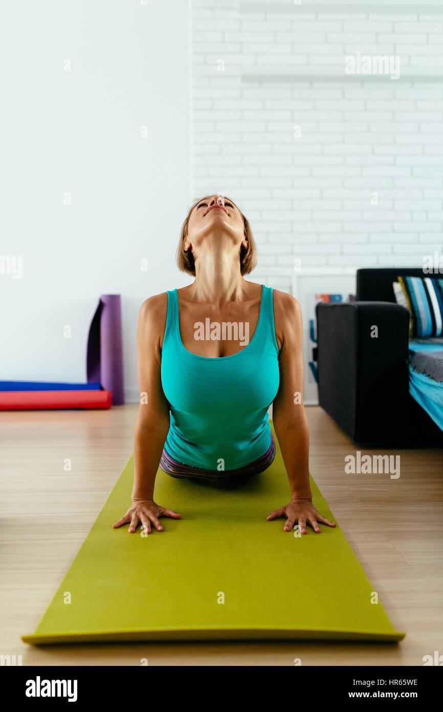Mujer atlética practicando yoga sobre una alfombra verde foto vertical interior. Imagen De Stock
