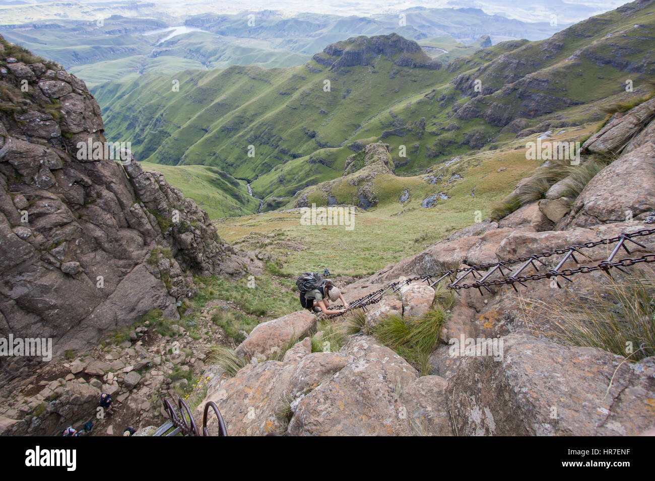 Un excursionista navega empinadas escaleras cadena levantarse un acantilado en el Parque Nacional Royal Natal, Sudáfrica Foto de stock