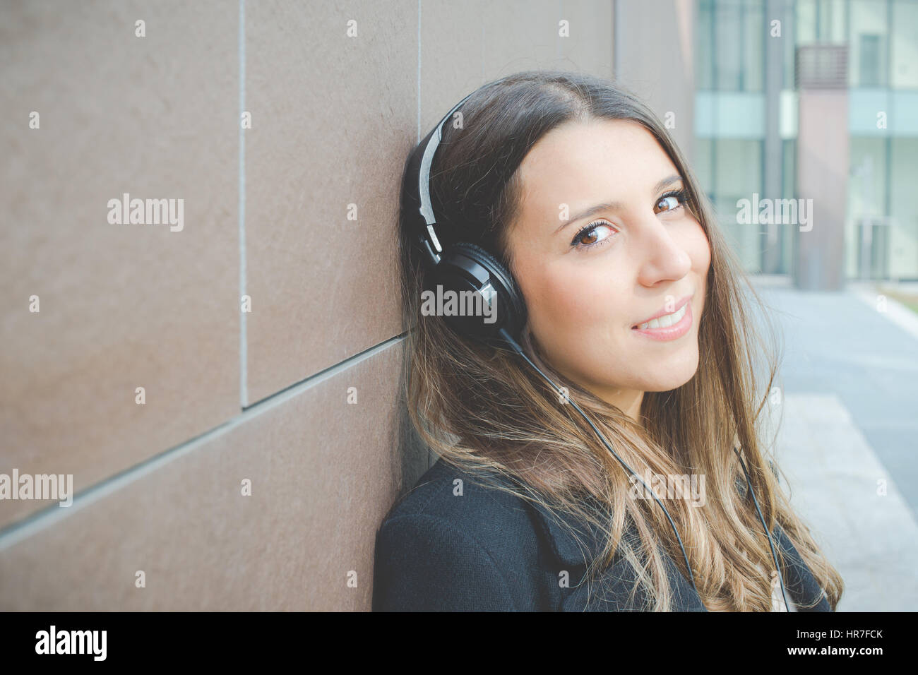 Joven mujer de negocios auténticos se relaja escuchando música en la ciudad Imagen De Stock