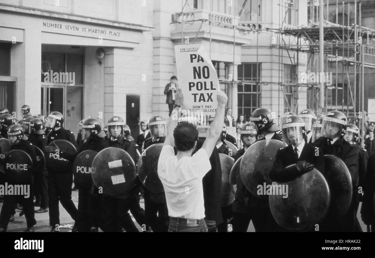 Un manifestante sostiene una pancarta a una línea de la policía antidisturbios durante el impuesto de encuesta disturbios Foto de stock