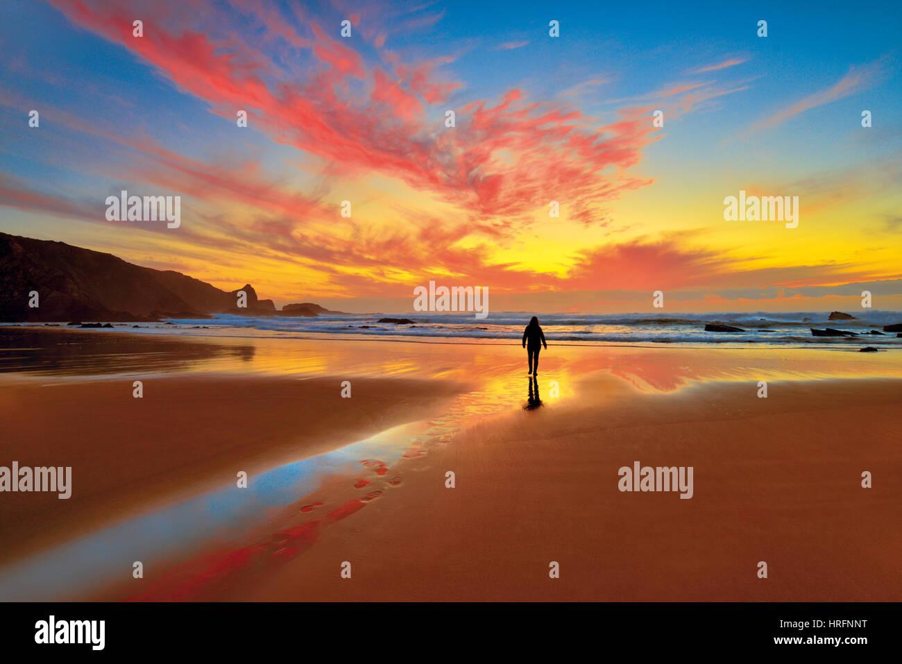 Sundown escénica con la mujer caminando sobre reflujo beach Foto de stock